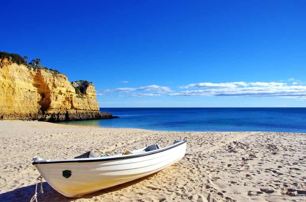 Fishing boat in the sand. Algarve, Portugal.