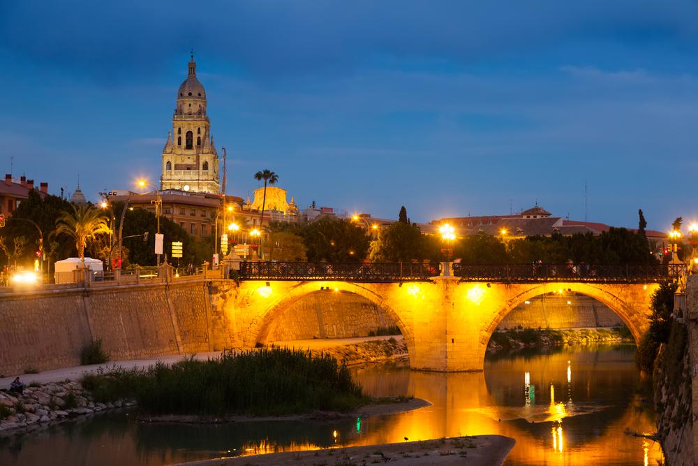 ancient stone bridge over Segura river in evening. Murcia, Spain